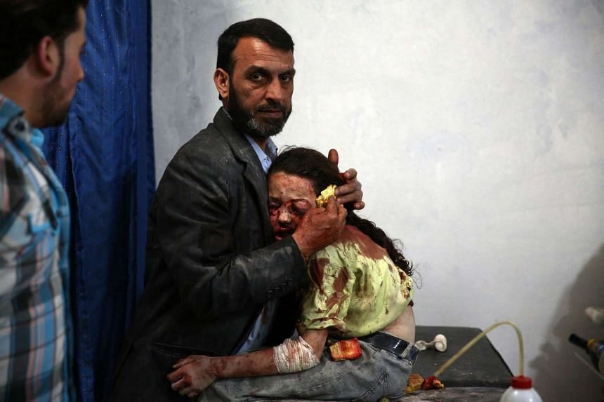 A wounded Syrian girl holds on to a relative as she awaits treatment by doctors, in one of Abd Doumany's photos.