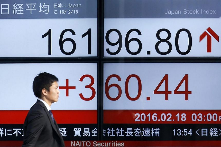 A businessman walks past a display showing closing information of Tokyo's Nikkei Stock Average in Tokyo, Japan, Feb 18, 2016.