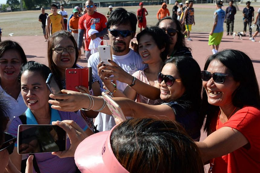Philippine boxing icon Manny Pacquiao (in white) posing for photos with fans in Mindanao on Feb 19, 2016.