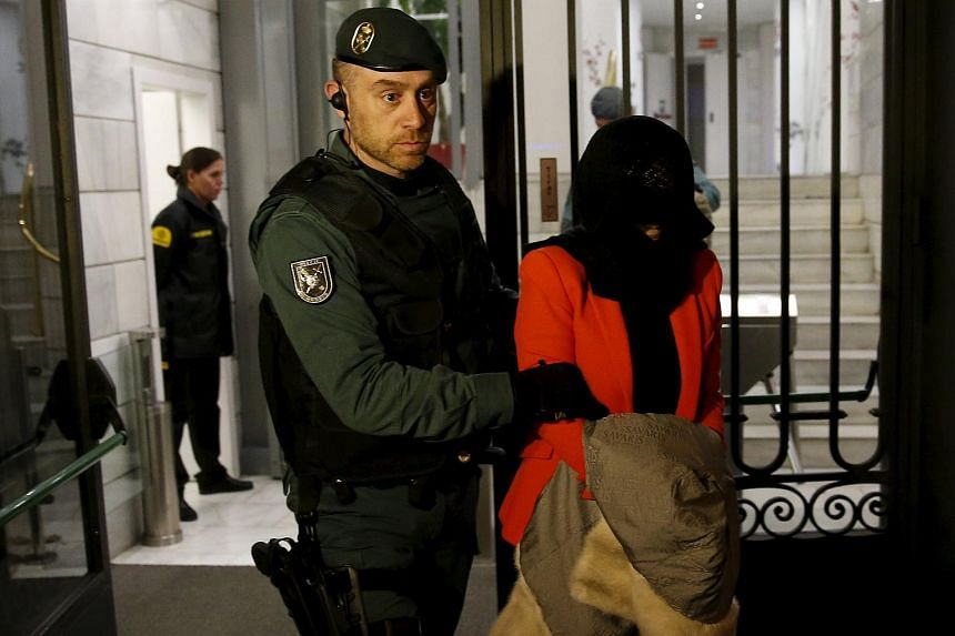 A suspect is led out of the ICBC headquarters in Madrid by a police officer on Feb 17.
