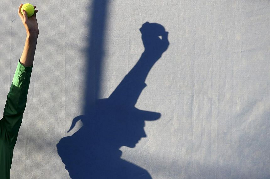 A ball boy is silhouetted as he holds up a tennis ball during a match at the Australian Open.