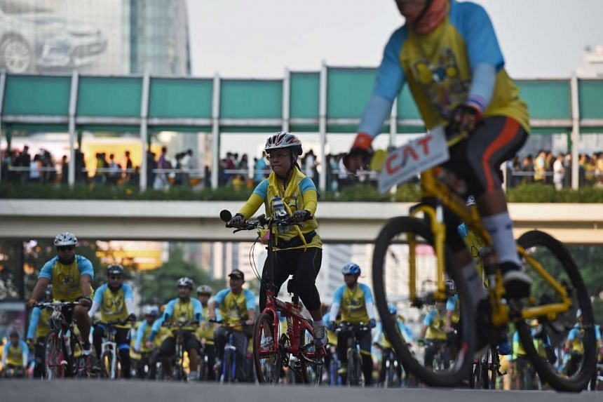 Cyclists at a mass event to honour King Bhumibol Adulyadej in Bangkok on Dec 11, 2015.