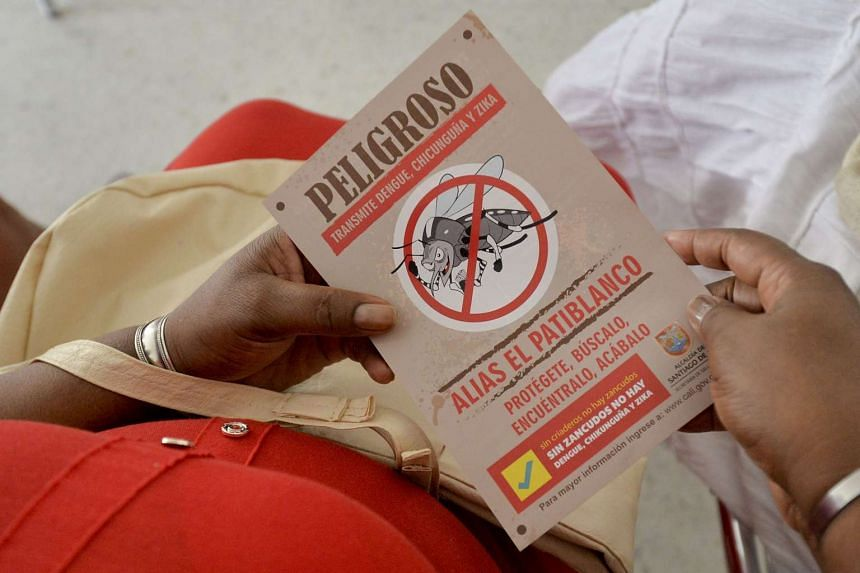 A woman holds a leaflet with information on the Aedes aegypti mosquito on Feb 17, 2016.