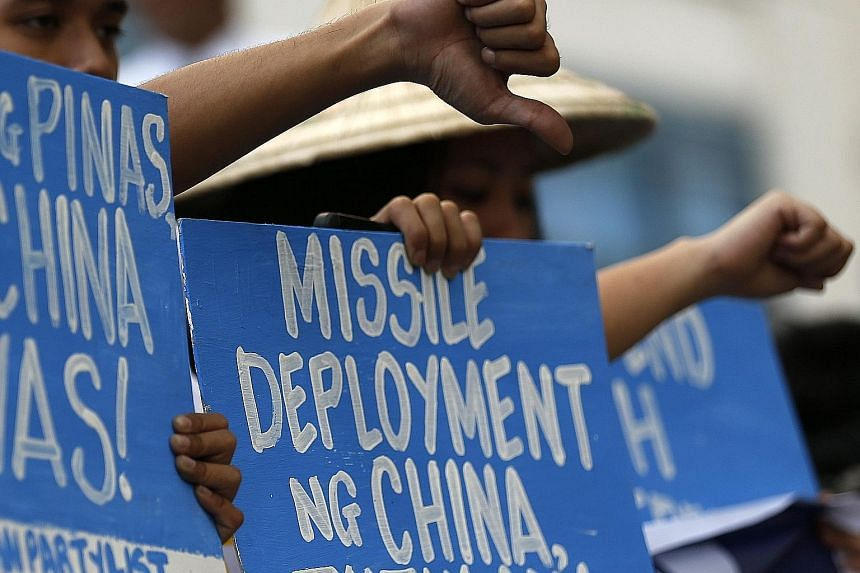 People staging a demonstration yesterday at the Chinese consular office in Makati city, south of Manila, to protest against China's apparent deployment of a surface-to-air missile system on Woody Island in the South China Sea. While Chinese officials