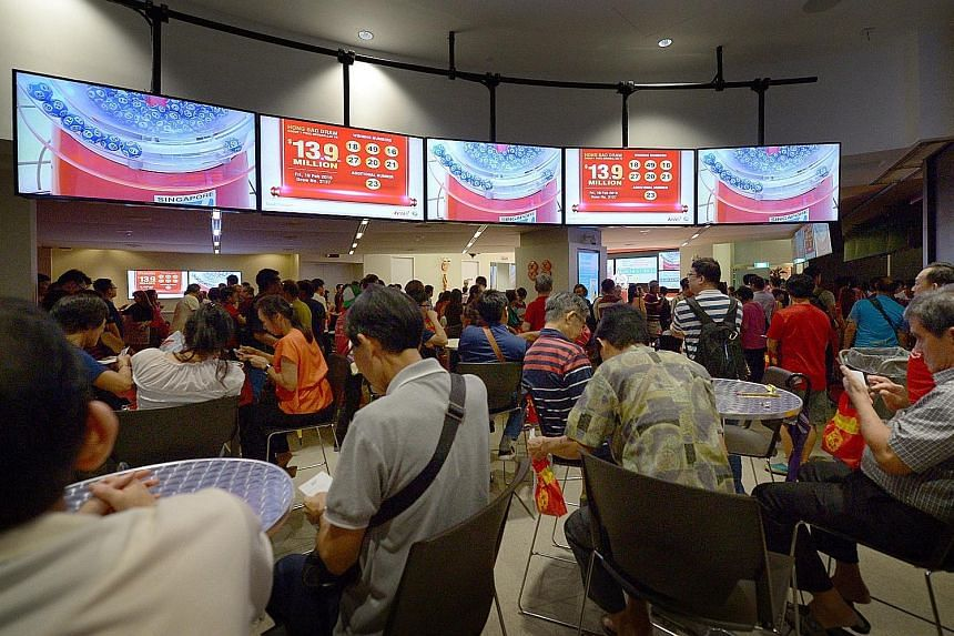 The crowd at the Singapore Pools main branch in Middle Road after the results for the Toto Hongbao Draw were announced last night. The $13.9 million prize will be shared between two winners, who bought their winning tickets in Marina Bay Sands mall a