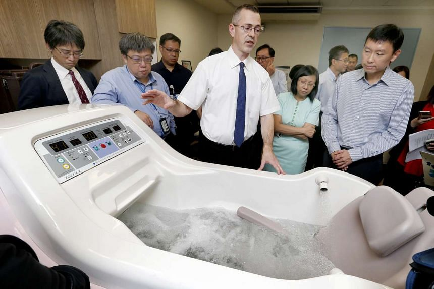 Senior Associate of International Sales Department from OG Wellness, Mr David Hale (centre), demonstrating use of the TUTTI Wheelchair Integrated Automated Bathing System. With him are (from left) Mr Masumitsu Tokuda, General Manager of International