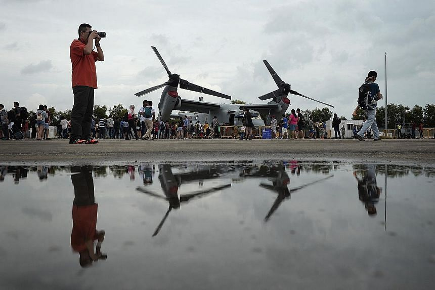 A queue (left) forms as visitors wait for a chance to sit in the cockpit of an F-15SG from the Republic of Singapore Air Force, probably the closest they will ever get to such a fierce fighter. It is not all strictly a display of macho military might