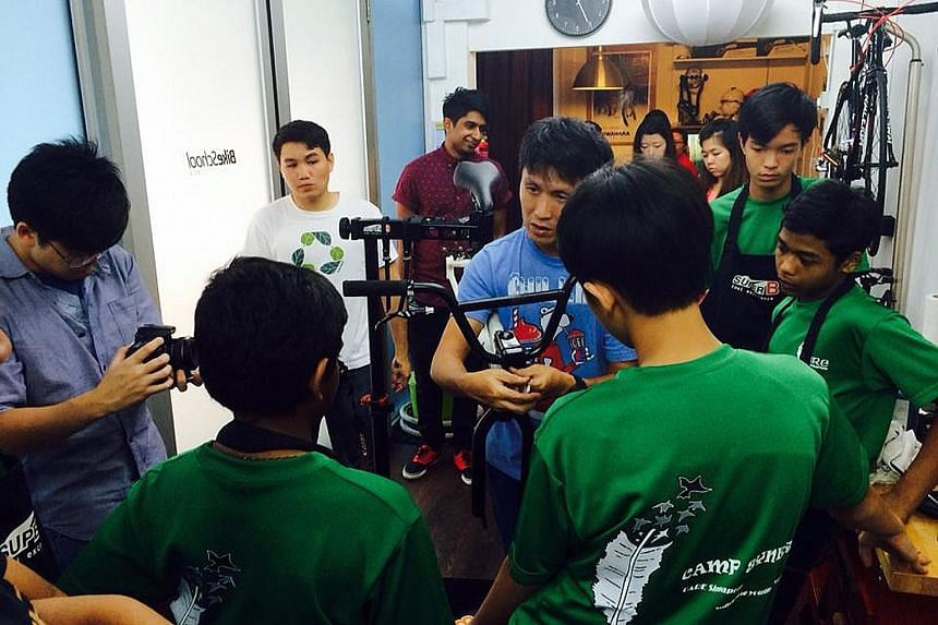 """Mr Wee working up a sweat on a bike trail in Tampines. The father of two girls now gets to spend more time with his family and says """"there is no stress when I'm done for the day"""". Mr Wee (at left, centre) conducting a bike mechanic clinic at his old"""