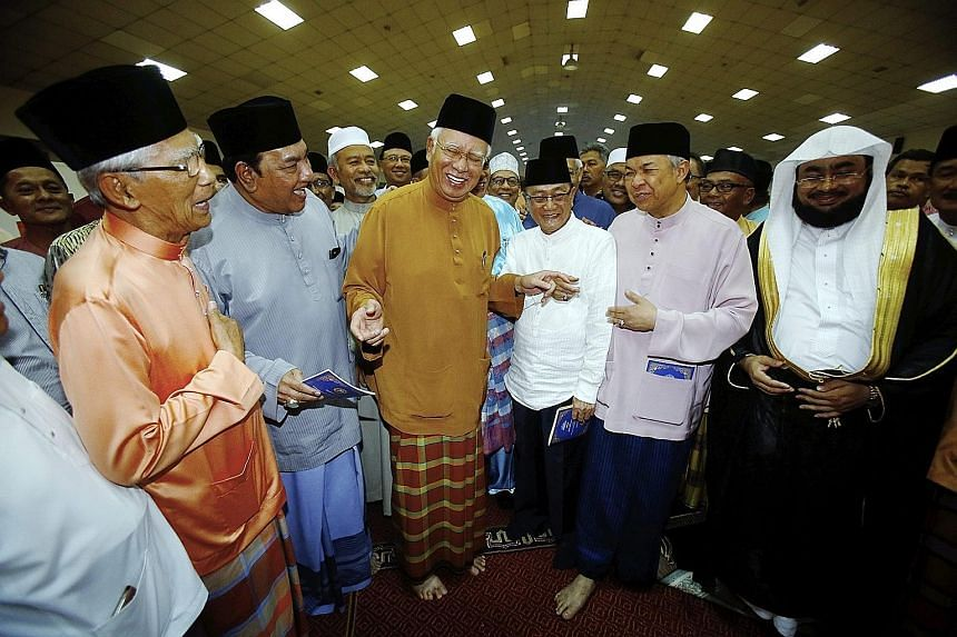 Malaysian Premier and Umno president Najib Razak (centre) was joined by other party members and guests including his deputy Ahmad Zahid Hamidi (second from right) and Sheikh Mohd Idris Mohd Al-Mashrafi, an imam from Mecca in Saudi Arabia (right), at