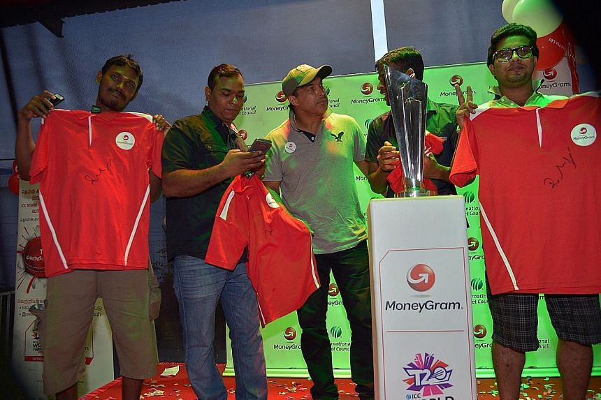 Cricket-crazy workers from India and Bangladesh pose with the ICC World T20 Trophy in Punggol yesterday and show off shirts signed by former Indian star Robin Singh (in cap). The ICC World T20 begins in India next month and the trophy arrived in Si