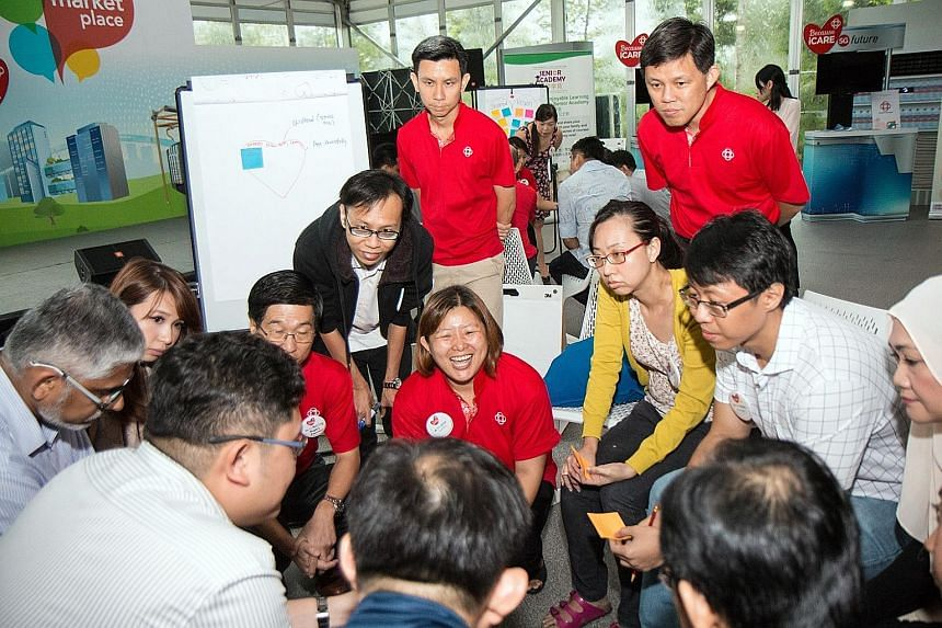 Minister in the Prime Minister's Office Chan Chun Sing (in red shirt, behind woman in yellow) at a session on Future Of Our Community in December, that was organised by the People's Association (PA). Mr Chan is also PA deputy chairman. Minister for C