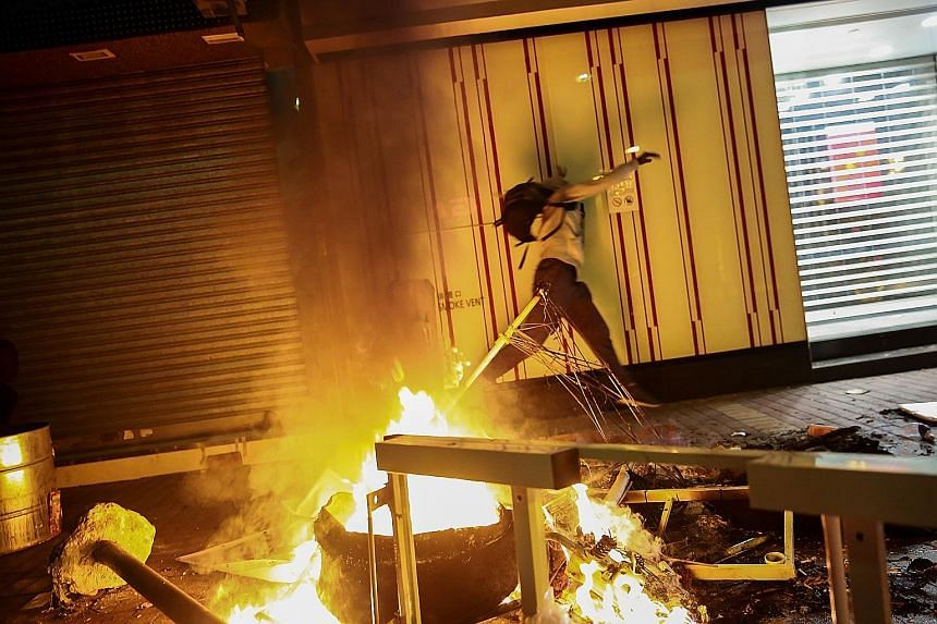 A rioter throwing an object during the violent Mongkok protest on Feb 9. In the worst conflict in Hong Kong since riots in the 1960s, protesters prised bricks from pavements to hurl at the police and set fire to bins and even a taxi. About 130 people