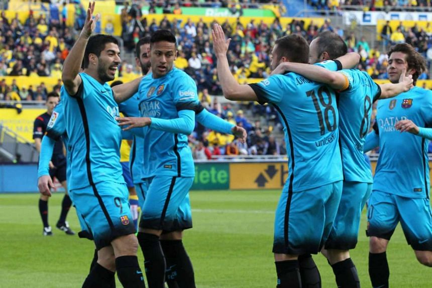 Suarez (left) celebrates a goal with Neymar (second left) and other teammates.