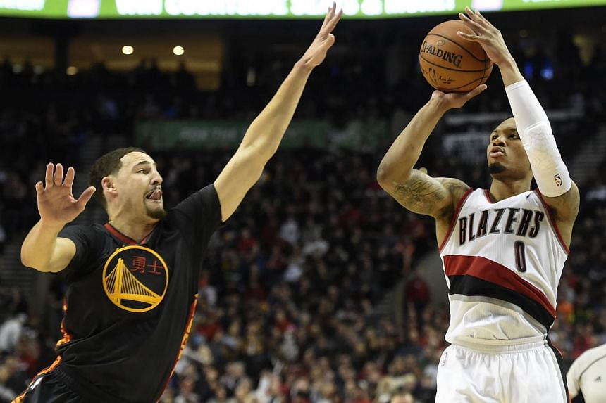 Portland Trail Blazers guard Damian Lillard (right) hits a three point shot over Golden State Warriors guard Klay Thompson.