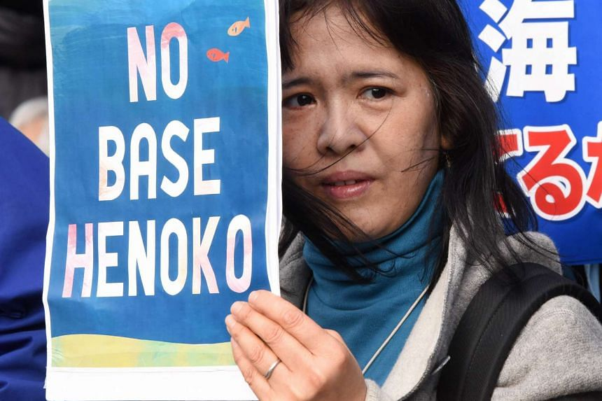 A woman holding a banner against the building of a US military base in Henoko in Japan's Okinawa prefecture, during a protest in Tokyo on Feb 21, 2016.