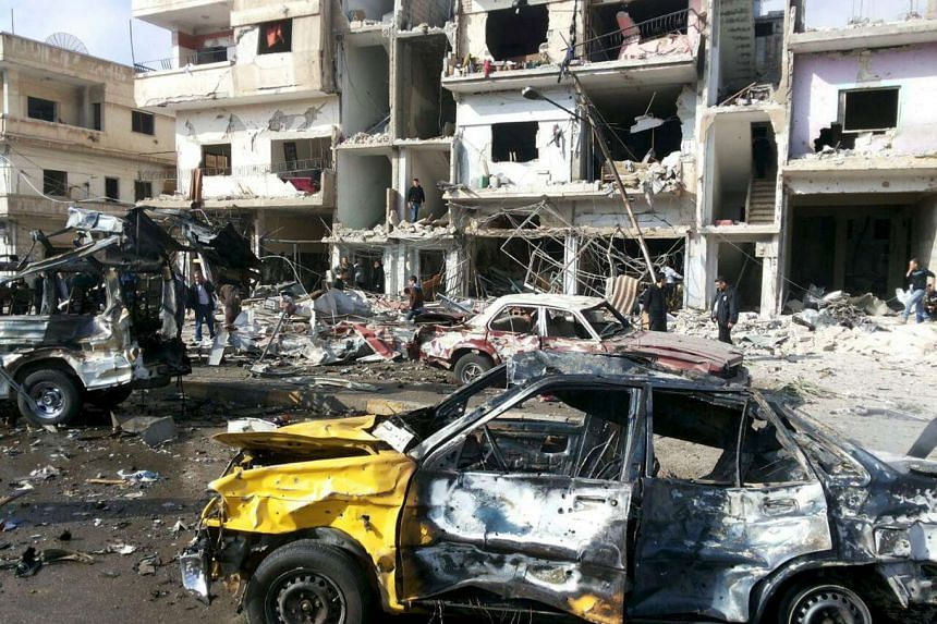 People inspecting the site of a twin bombing in the government-controlled city of Homs, Syria, on Feb 21, 2016.