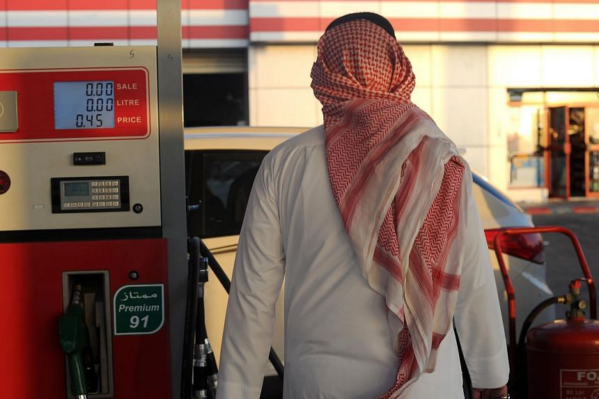 A Saudi man walks past a pump at a petrol station on Dec 28, 2015 in Jeddah.
