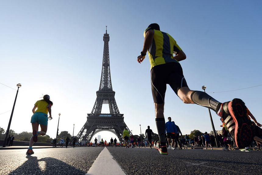 Runners (above) warming up by the Eiffel Tower.