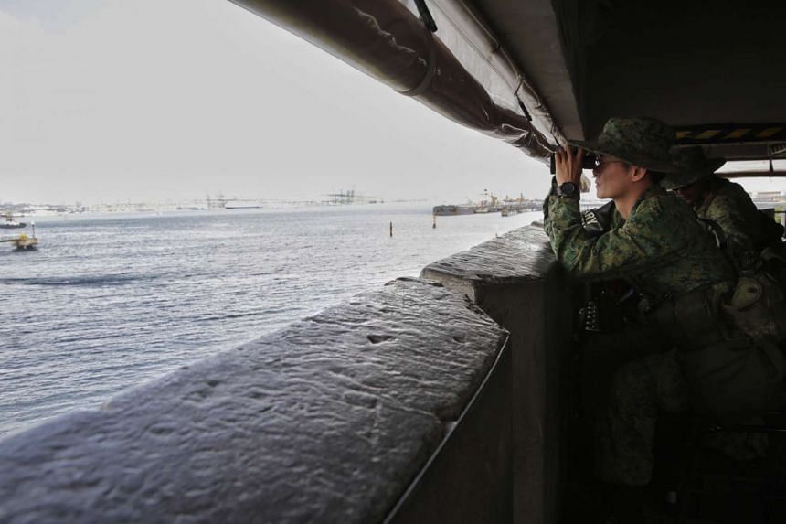 Security trooper 3SG Chia Yong Guan, 38, looking out from an observation tower in Jurong Island on Feb 22, 2016.