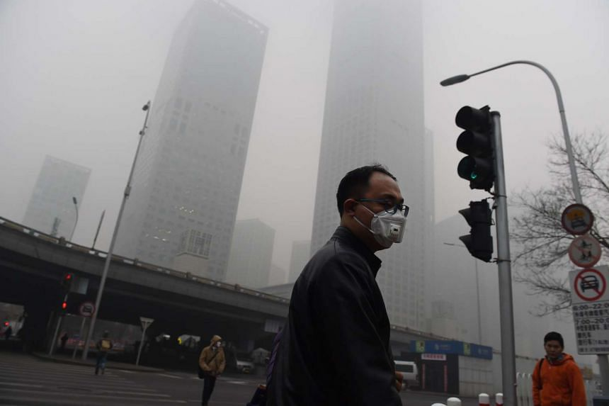 A man wears a mask on a heavily polluted day in Beijing on Dec 22, 2015. The Chinese capital imposed the highest tier of a four-colour smog warning system for four days starting Dec 19.