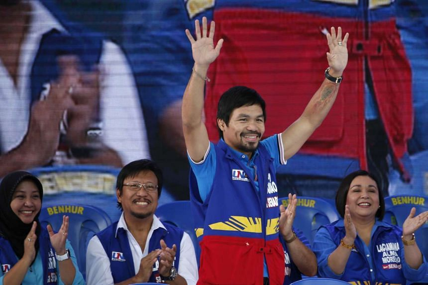 Filipino boxer and senatorial candidate Manny Pacquiao waves to supporters in Mandaluyong city, Philippines on Feb 9, 2016.