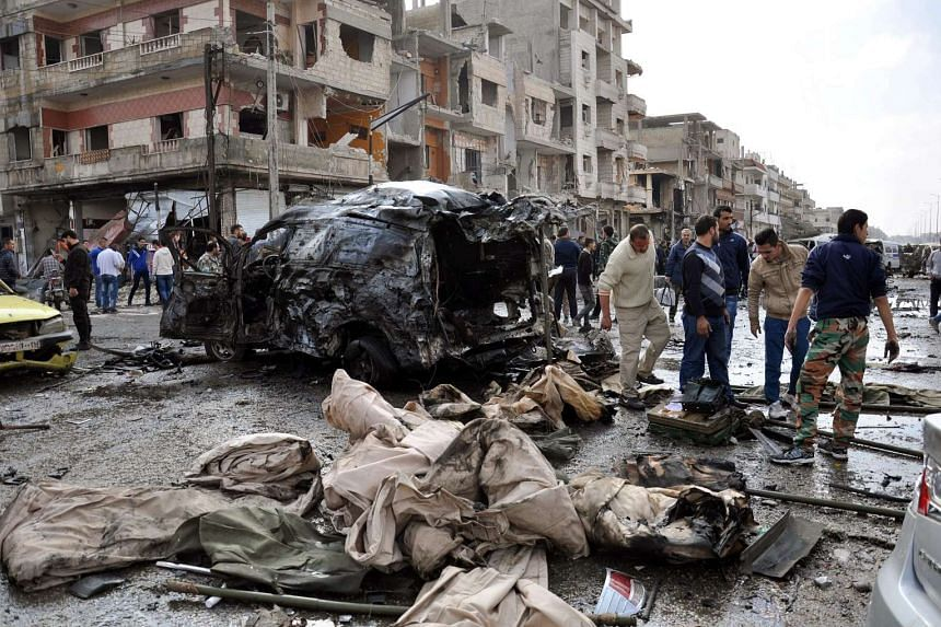 Syrian policemen and citizens inspect the site of a twin bomb attack in the city of Homs, Syria on Feb 21, 2016.