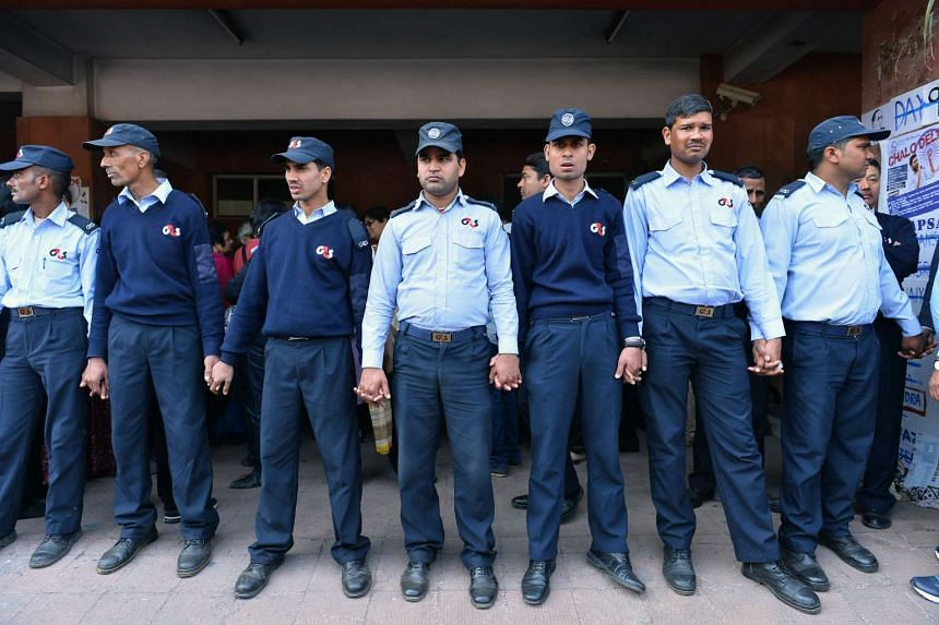 Private security guards stand in a line in front of Indian student activist Umar Khalid (unseen) at Jawaharlal Nehru University in New Delhi on Feb 22, 2016.