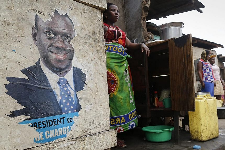 Stallholders in Kampala, Uganda, awaiting the results of the presidential election last Saturday. President Yoweri Museveni beat seven rivals, including opposition leader Kizza Besigye (pictured in poster) to win his fifth term.