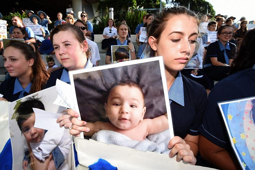 Students hold photographs of a baby Asha during a protest outside the Lady Cilento Children's Hospital in Brisbane, on Feb 18, 2016.