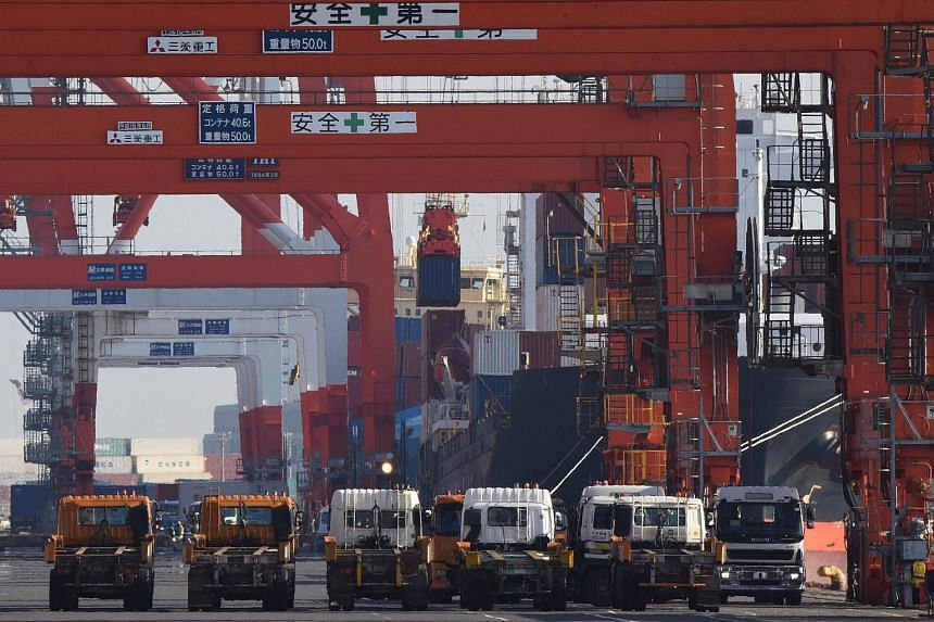 A container is loaded onto a cargo ship at a pier in Tokyo, on Feb 18, 2016.