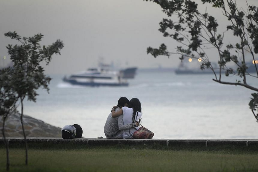 A young couple embraces at East Coast Park.