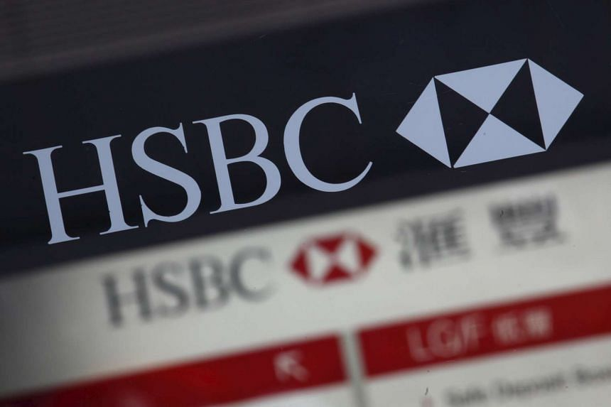 Company logos of HSBC are displayed at the entrance and inside one of its branches in Hong Kong, China.