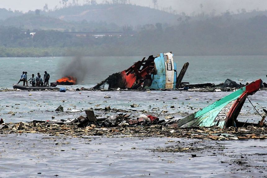 Indonesia Navy personnel inspect the wrackage of foreign fishing vessels after blowing it up at Batam Sea, Indonesia on Feb 22, 2016.