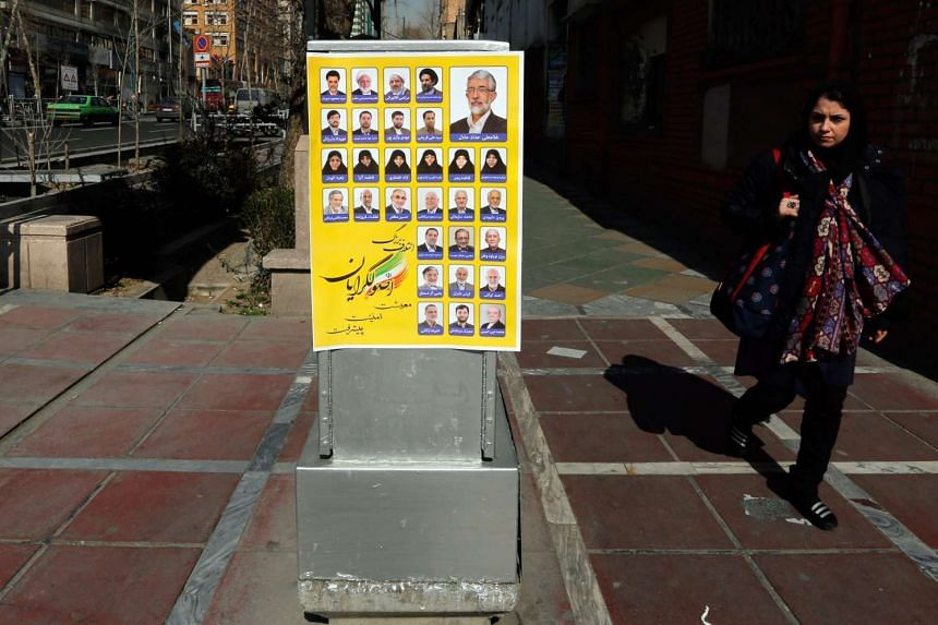 An Iranian woman walks next to election posters in a street of Teheran on Feb 18, 2016.