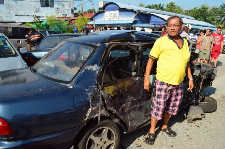 An owner of one of the damaged vehicles with his car.