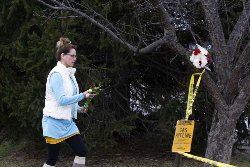 A woman places flowers at a Cracker Barrel where a gunman went on a shooting rampage, on Sunday (Feb 21) in Kalamazoo, Michigan.