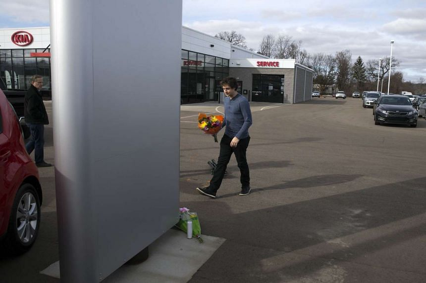 A man places flowers at Kia Dealship where a gunman went on a shooting rampage on Sunday (Feb 21) in Kalamazoo, Michigan.