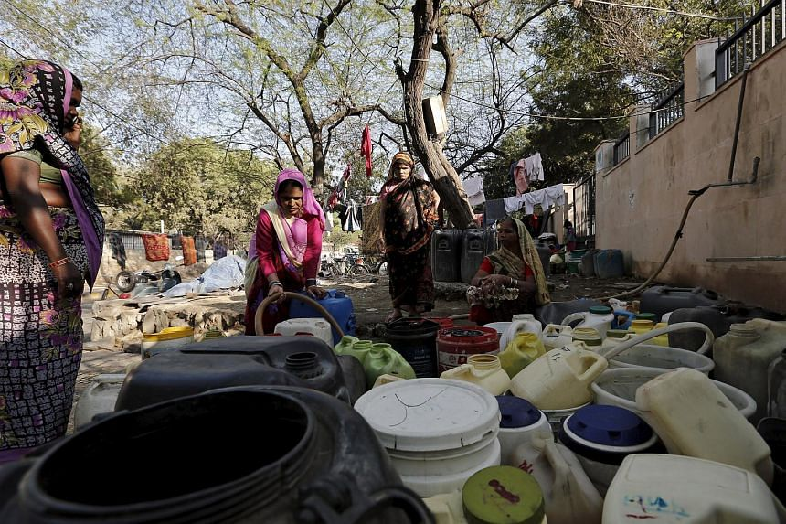 Women fill water in their containers from a municipal tap in New Delhi, India, on Feb 21, 2016.
