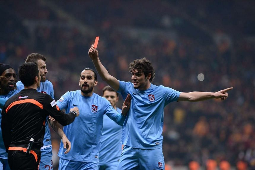 Trabzonspor's Salih Dursun (right) showing a red card to referee Deniz Ates Bitnel.