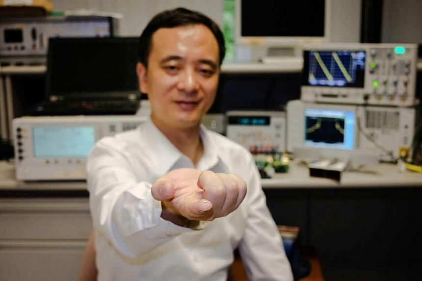 Assistant Professor Zheng Yuanjin from NTU's School of Electrical and Electronic Engineering with the radar camera microchip on his finger.