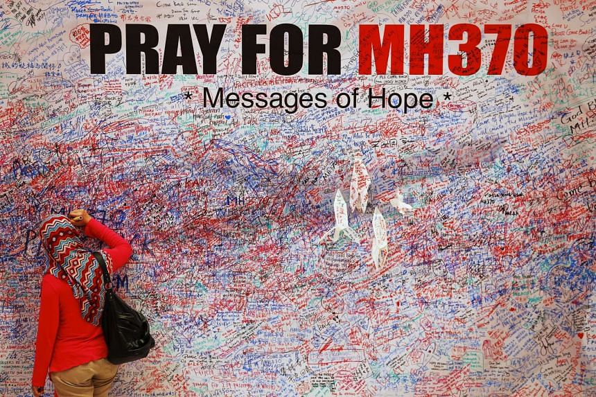A woman in Kuala Lumpur leaves a message of support for passengers of the missing MH370 flight.