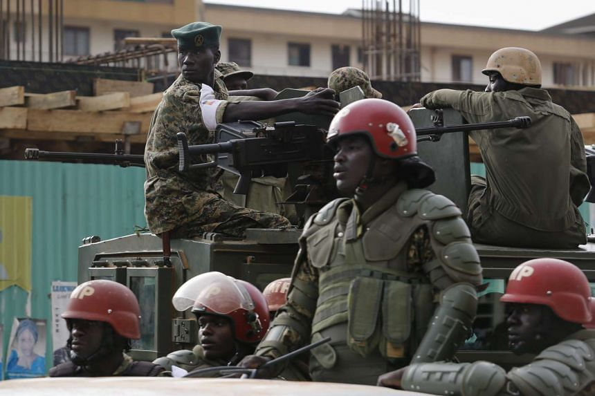 Army soldiers stand guard against supporters of opposition leader Kizza Besigye in Kampala, Uganda.
