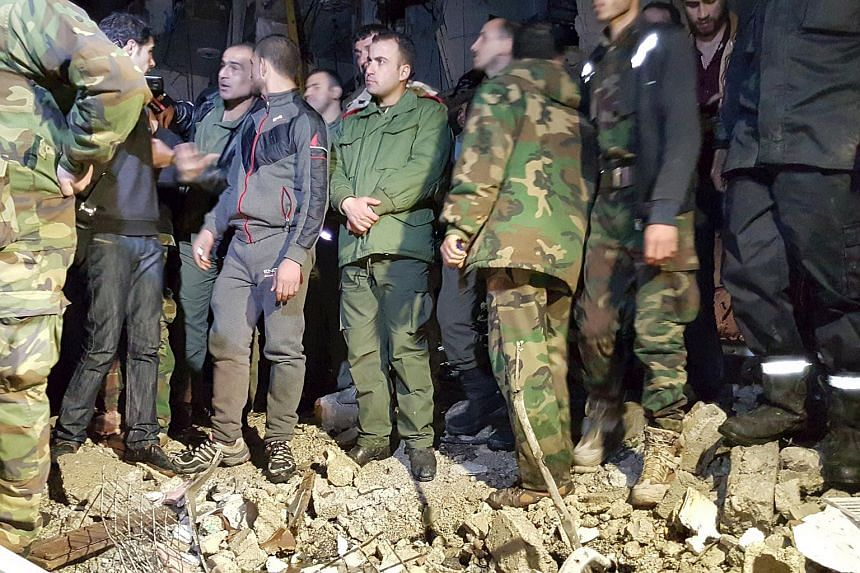 Syrian army soldiers and civilians inspect the site of multiple bomb blasts in Damascus on Feb 21, 2016.