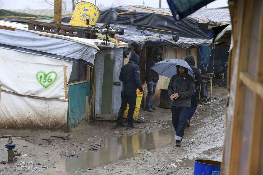 "Migrants walk in the mud in the southern part of a camp for migrants called the ""jungle"" in Calais."