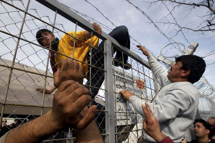 A migrant attempts to climb the border fence from Greece to Macedonia.