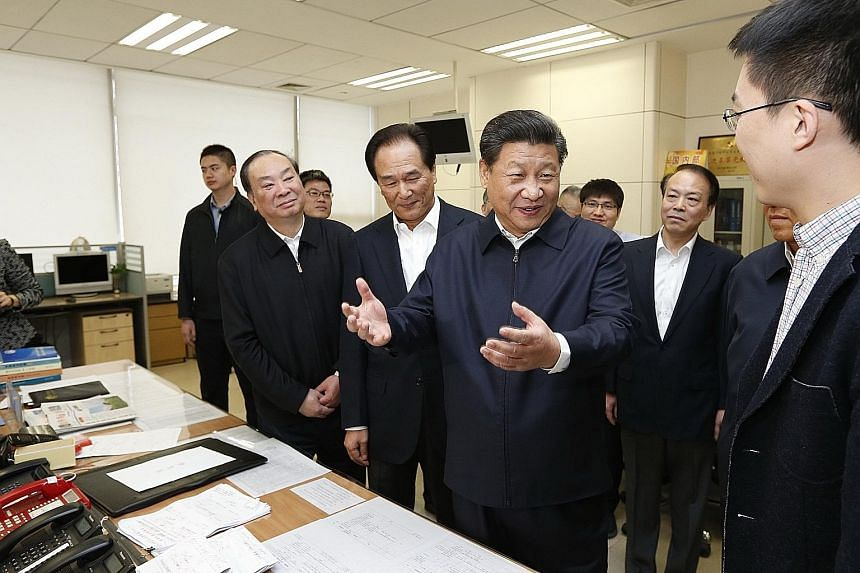Chinese President Xi Jinping (centre) talking to a correspondent at the headquarters of Xinhua news agency in Beijing last Friday. Mr Xi also visited the People's Daily and CCTV the same day.