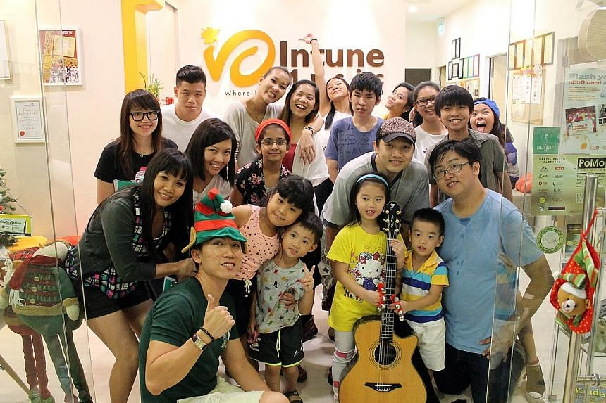 A rehearsal held at Intune Music School in December involving instructors, students, parents and members of NTUC's youth group nEbO. The school has an annual revenue of between $700,000 and $800,000. Mr Lim (foreground, left with hat), its founder an