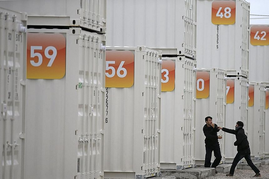 Migrants having a light moment outside shipping containers that have been converted into homes at a state-run shelter near Calais, France, yesterday. Portugal has offered to take up to 10,000 migrants from Austria, Greece, Italy and Sweden - countrie