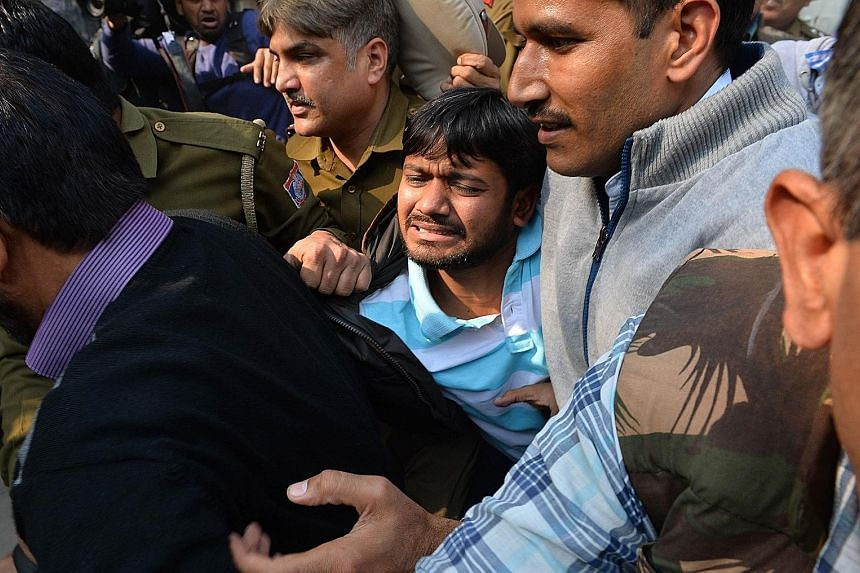 Police escorting student union leader Kanhaiya Kumar (centre) to a court in Delhi last Wednesday. The five students who emerged from hiding yesterday were wanted since the arrest of Kumar.