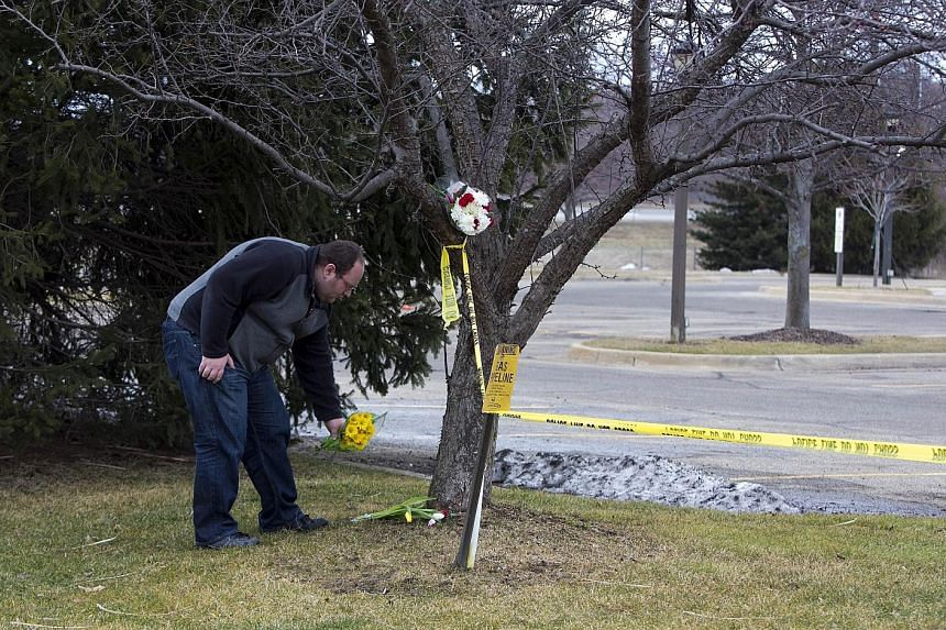 A grieving man outside the Cracker Barrel restaurant on the interstate highway near Kalamazoo. Four women were fatally shot, and a teenage girl gravely injured, as they sat in their cars outside the restaurant last Saturday. This was just minutes aft